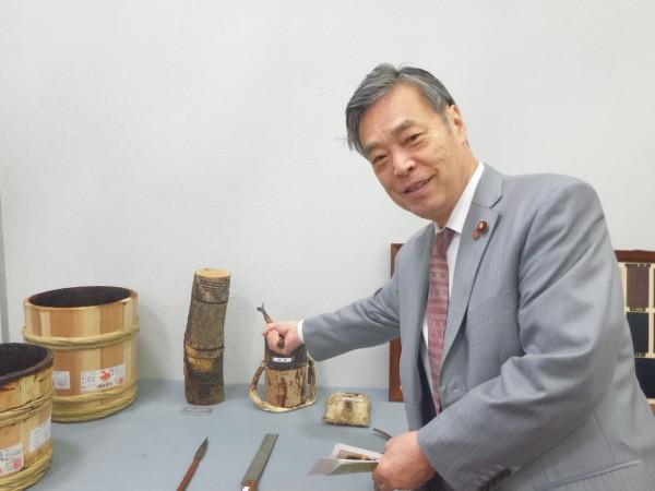 漆かきの道具も展示されています。左はかいた漆を入れる桶です。その左は漆の木。右手に持っているのは漆をかきとる道具です。